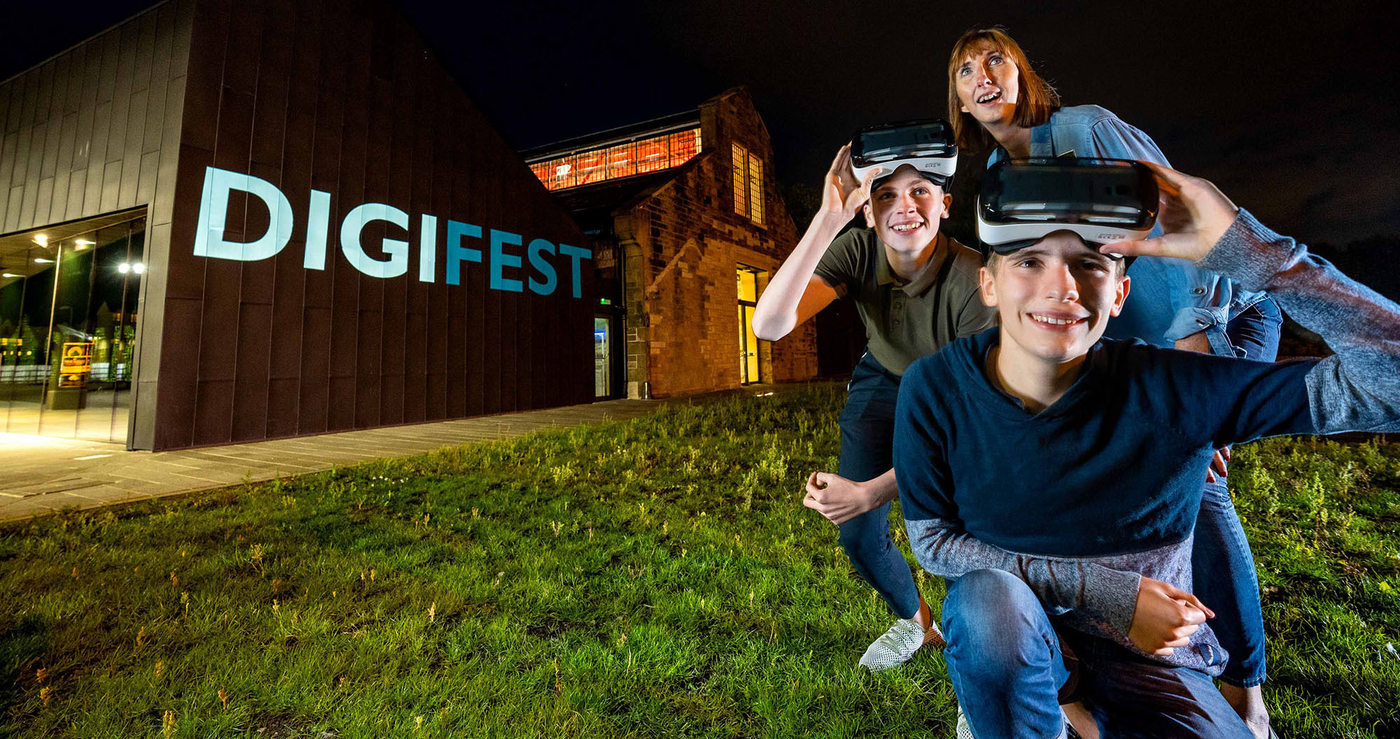 An adult and two boys stand outside the Engine Shed at night wearing VR headsets and smiling