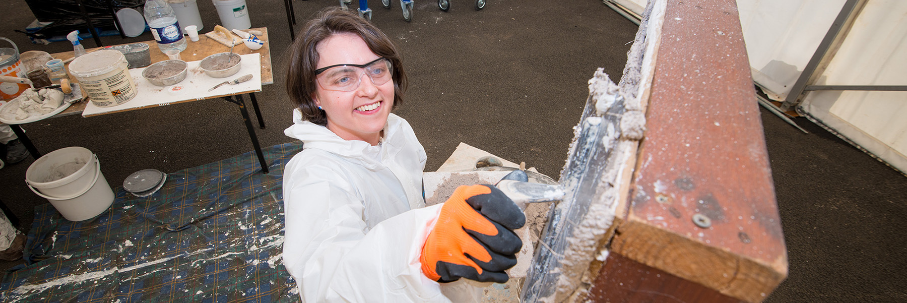 A photo of someone learning how to do traditional plastering, smiling and looking up towards the camera